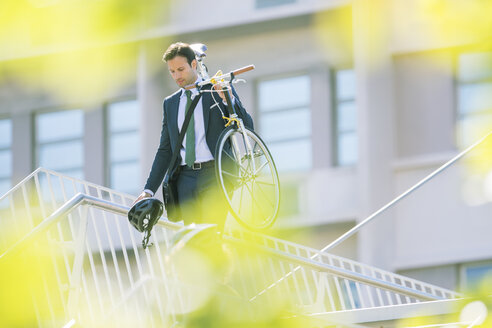 Businessman in suit carrying bicycle in city - CAIF12187