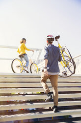 Man in helmet carrying bicycle up urban stairs - CAIF12193