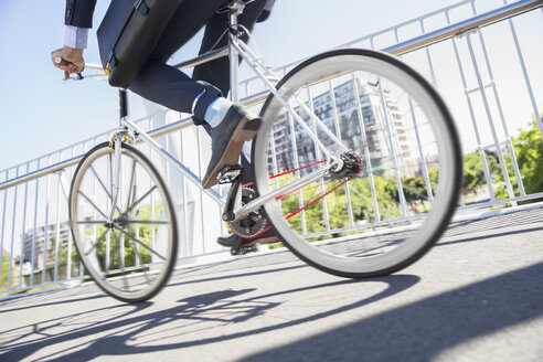 Low section businessman in suit riding bicycle on sunny urban sidewalk - CAIF12196