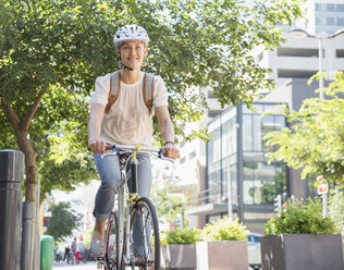Portrait smiling young woman in helmet riding bicycle in urban park - CAIF12199