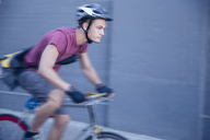 Focused bicycle messenger with helmet on the move - CAIF12202