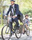 Businessman in suit and helmet riding tandem bicycle with son - CAIF12205