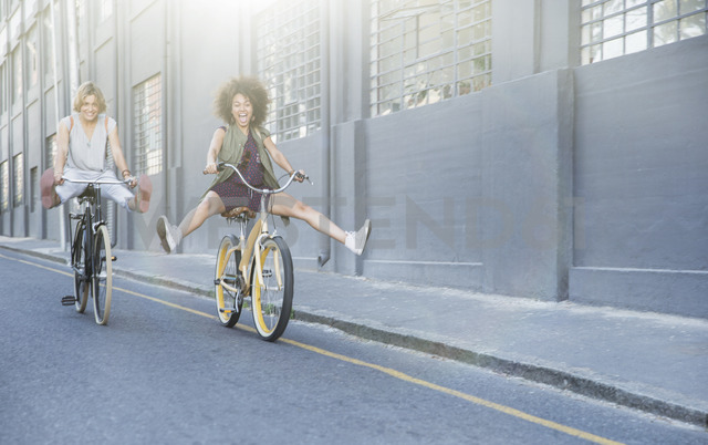 Playful women coasting on bicycles down urban street - CAIF12214