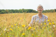Senior woman meditating in rural field - CAIF12223