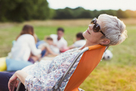 Senior woman relaxing in chair in field - CAIF12226