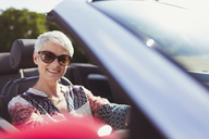 Portrait smiling senior woman in sunglasses driving convertible - CAIF12232