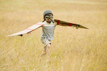 Boy running with wings and aviator's cap and flying goggles in field - CAIF12289
