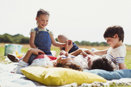 Family relaxing on blanket in sunny field - CAIF12298