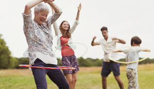 Playful multi-generation family spinning in plastic hoops in field - CAIF12313