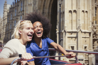 Enthusiastic friends laughing on double-decker bus in London - CAIF12328