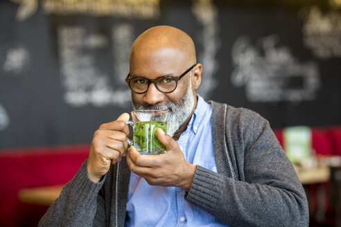 Portrait of smiling man with glass of tea in a coffee shop - FMKF04905