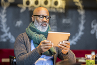 Portrait of man using tablet in a coffee shop - FMKF04908