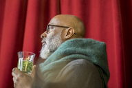 Profile of pensive man with glass of tea - FMKF04911
