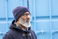 Portrait of man wearing blue woolly hat watching something - FMKF04914