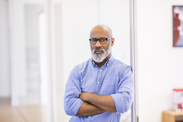 Portrait of bald businessman with beard and glasses in the office - FMKF04929