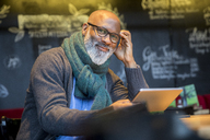 Portrait of smiling man with tablet in a coffee shop - FMKF04944