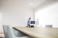 Businessman in conference room preparing a presentation - FMKF04956