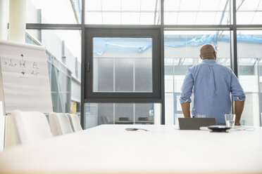 Rear view of businessman with flip chart in conference room - FMKF04959