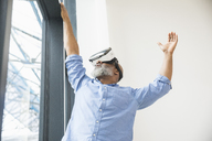 Businessman wearing VR glasses at the window - FMKF04962
