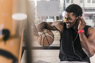 Smiling man with tattoos and basketball using smartphone and earphones - UUF12979