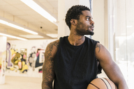 Man with tattoos holding basketball looking away - UUF12985