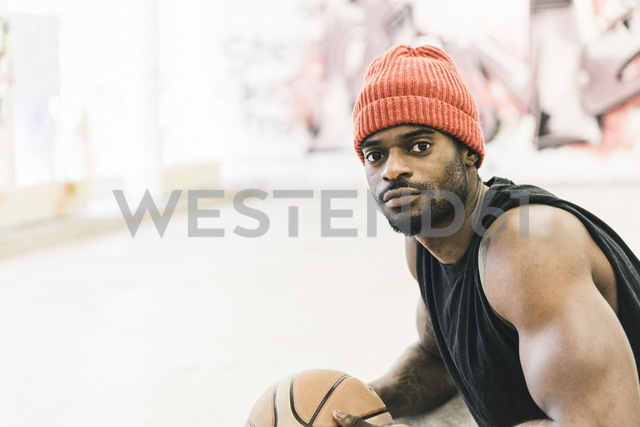 Man with tattoos and woolly hat holding basketball - UUF12988