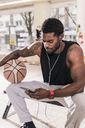 Man with tattoos and basketball using smartphone and earphones - UUF13000