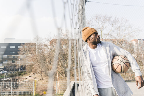 Basketball player on court leaning against fence - UUF13006