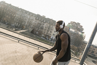 Basketball player with headphones in action on court - UUF13012