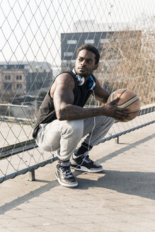 Basketball player on court crouching at fence - UUF13015