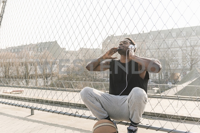 Basketball player on court crouching at fence listening to music - UUF13018