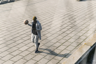 Young man with basketball walking on a square - UUF13021