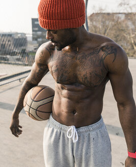 Portrait of muscular barechested basketball player standing on court - UUF13039
