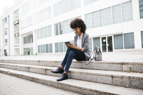 Smiling woman sitting on stairs outdoors using cell phone - JRFF01606