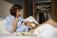 Woman looking dog while relaxing on bed - CAVF05618