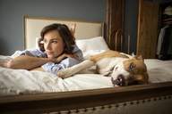 Woman with dog resting on bed at home - CAVF05621