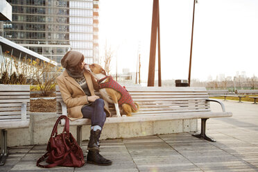 Woman kissing dog while sitting on bench against office building - CAVF05630