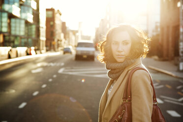Woman looking away while walking on road in city - CAVF05636