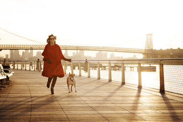 Woman running with dog on promenade against Williamsburg Bridge - CAVF05639