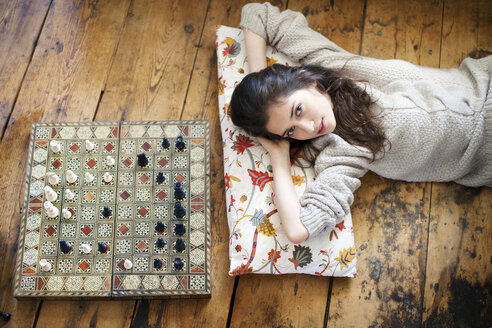 Portrait of woman lying on floor by chess board at home - CAVF05750