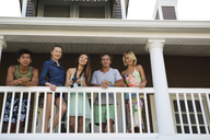 Portrait of friends standing in balcony at beach house - CAVF05882