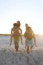 Men piggybacking women while walking on sand at beach - CAVF05891