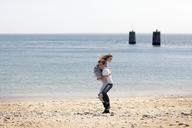 Man lifting girlfriend while standing on shore beach - CAVF06002