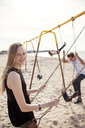 Portrait of woman playing swing at beach - CAVF06044