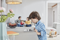 Boy looking at tablet at home with family in background - RORF01123