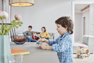 Boy looking at tablet at home with family in background - RORF01126