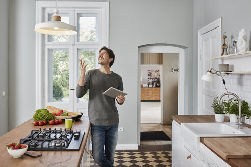 Happy man using tablet in kitchen looking at ceiling lamp - RORF01129