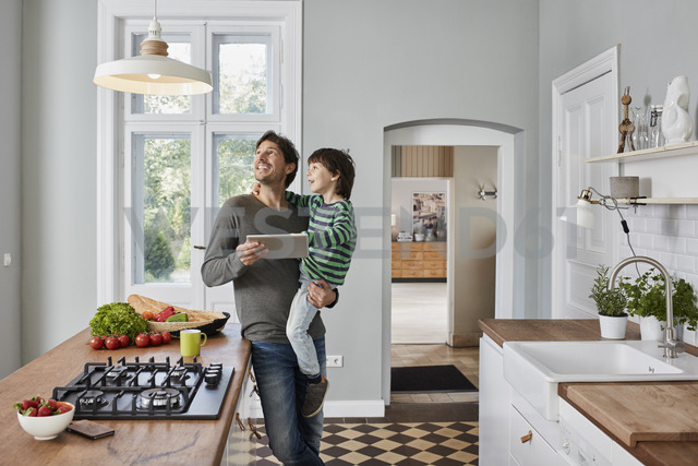 Father and son using tablet in kitchen looking at ceiling lamp - RORF01132 - Roger Richter/Westend61