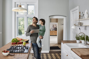 Father and son using tablet in kitchen looking at ceiling lamp - RORF01132