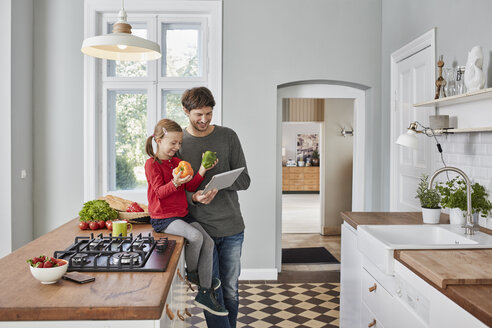 Smiling father and daughter with bell pepper and tablet in kitchen - RORF01135